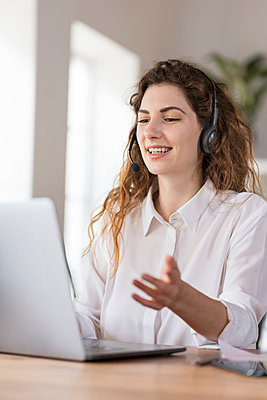 Contented female customer service representative with headphones explaining to client headphones at desk in home office - p300m2277532 by Steve Brookland