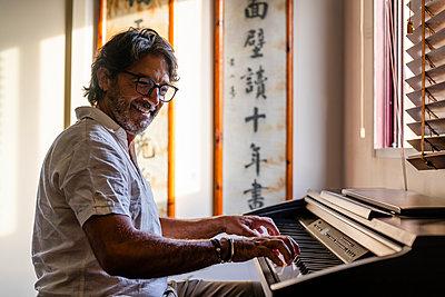 Smiling mature man playing piano at home - p300m2298970 von Javier De La Torre