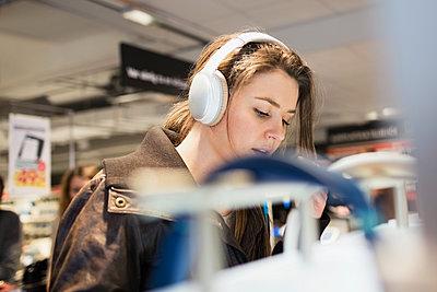 Female customer listening headphones at electronics store - p426m1147972 by Maskot