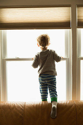 Caucasian boy looking out window - p555m1410638 by Roberto Westbrook