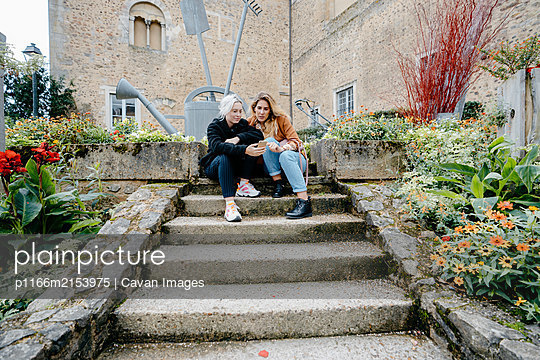 Young women using their smartphone sitted on stairs in a french town - p1166m2153975 by Cavan Images