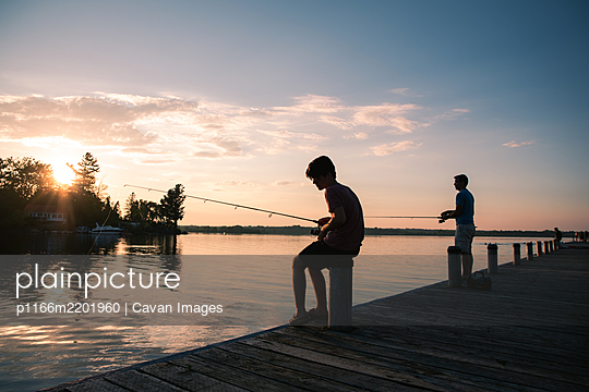 Father and son fishing on a dock of lake at sunset in Ontario, Canada. - p1166m2201960 by Cavan Images