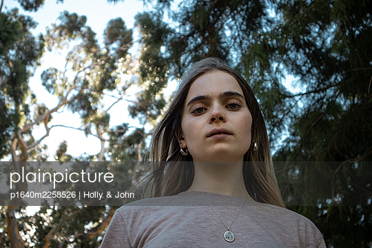 Portrait of teenage girl in a park - p1640m2258526 by Holly & John
