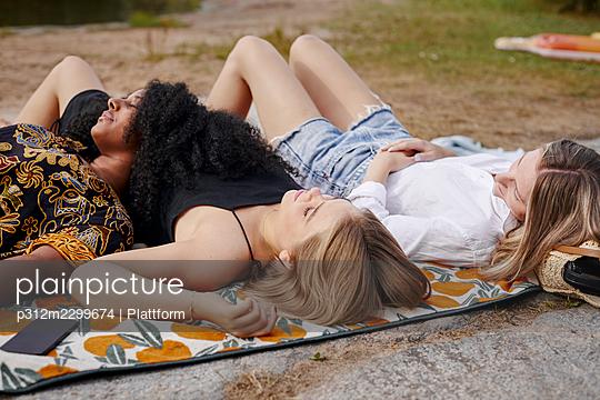 Three friends lying on blanket - p312m2299674 by Plattform
