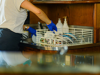 Female bar tender barista washing and cleaning cups and dishes - p1166m2201358 by Cavan Images
