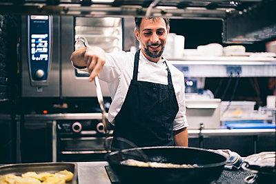 Cook at work in a restaurant kitchen - p300m2144259 von Oscar Carrascosa Martinez