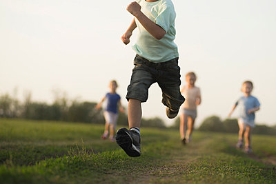 Low view of a boy running in a field with other children behind - p301m714385f by Vladimir Godnik