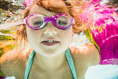 Caucasian girl swimming underwater in swimming pool - p555m1411537 by John Fedele