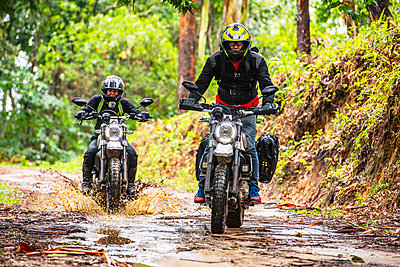 Bikers riding off road motorcycle on dirt road through forest, Chiang Mai, North Thailand - p924m2145357 by Henn Photography