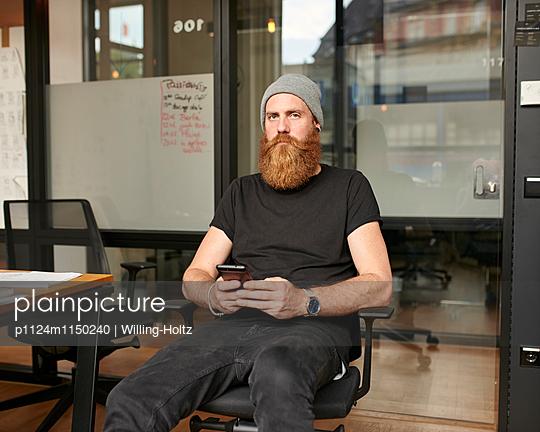 Mann mit Smartphone am Arbeitsplatz - p1124m1150240 von Willing-Holtz