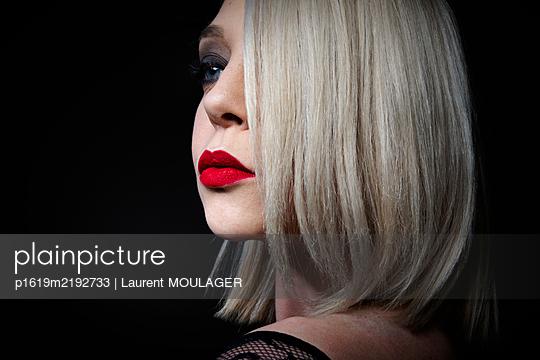 Junge blonde Frau mit rotem Lippenstift - p1619m2192733 von Laurent MOULAGER