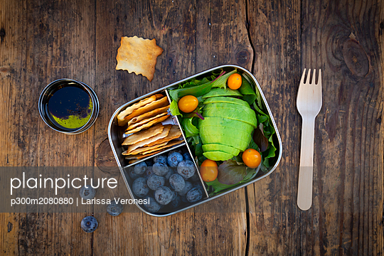 Lunch box of leaf salad, avocado, blueberries, tomatoes and crackers - p300m2080880 by Larissa Veronesi