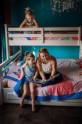 Mother reading book while sitting with daughters on bunkbed at home - p1166m1568776 by Cavan Images