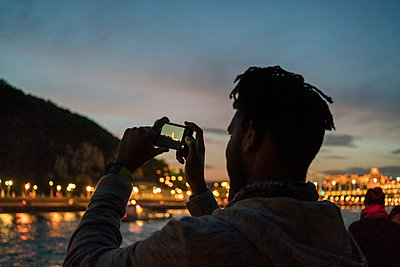 African male taking image from a boat at night in Budapest - p1166m2171841 by Cavan Images