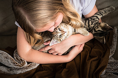 Young Girl Looking Down Holding Kittens on Brown Blanket - p1166m2207865 by Cavan Images