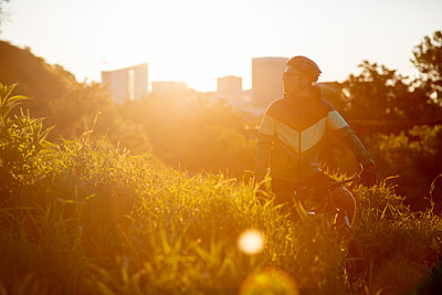 Mountain biker at sunrise with Richmond skyline in the background. - p1166m2269642 by Cavan Images