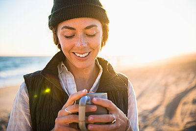 Young woman enjoying drink in mug while beach car camping alone - p1166m2285580 by Cavan Images