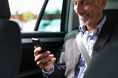 Male business professional using smart phone in car - p300m2287636 by Emma Innocenti