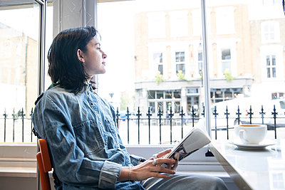 Young woman sitting with book in cafe looking through window - p300m2290732 by Pete Muller