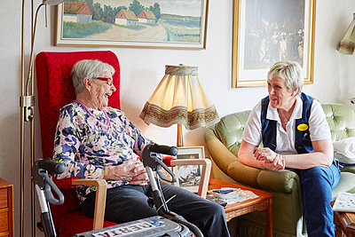 Senior woman talking with nurse in care home - p312m1054506f by Jan Tove