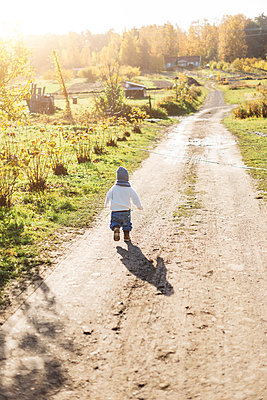 Rear view of little boy playing on a rural road in Sweden - p352m1536611 by Calle Artmark