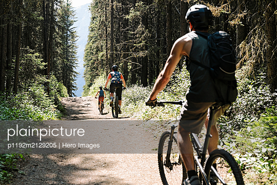 Friends mountain biking on trail in sunny woods - p1192m2129205 by Hero Images