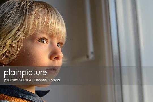 Little boy looking out of window - p1631m2260164 by Raphaël Lorand