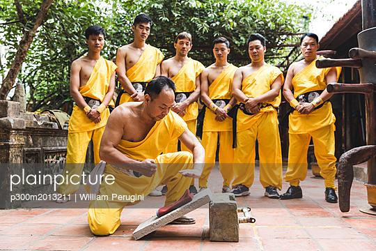 Vietnam, Hanoi, men exercising kung fu, man on flagstone - p300m2013211 von William Perugini