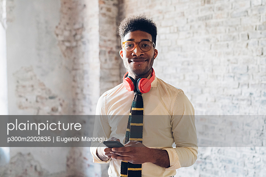 Portrait of smiling young man holding smartphone in loft - p300m2202835 by Eugenio Marongiu