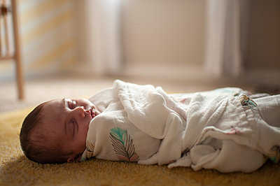Newborn baby girl wrapped up in blanket sleeping at home - p1166m2136694 by Cavan Images