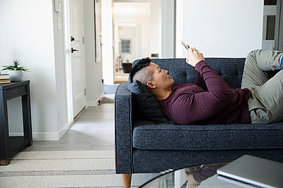 Man relaxing, using smart phone on living room sofa - p1192m2088550 by Hero Images