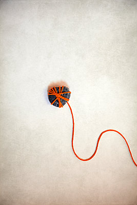 Pebble wrapped in a red string  - p1248m2270284 by miguel sobreira