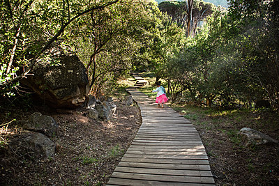 Little girl walking on planked footpath - p1640m2246845 by Holly & John