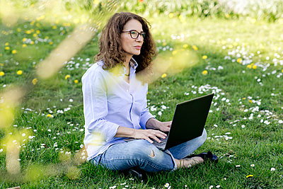 Woman sitting on a meadow using laptop - p300m2188572 by FL photography