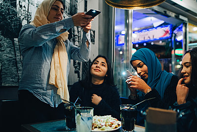 Young Muslim females photographing food and drinks on table with friends at cafe - p426m1556082 by Maskot