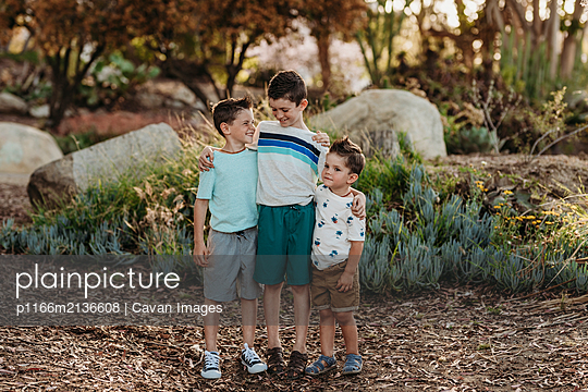 Portrait of three brothers smiling at each other in cactus garden - p1166m2136608 by Cavan Images