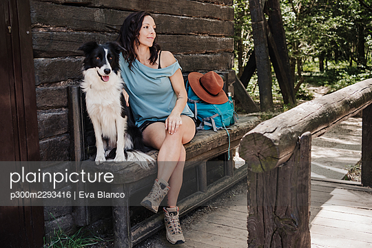 Female tourist sitting with pet dog on bench by cottage in forest - p300m2293416 by Eva Blanco