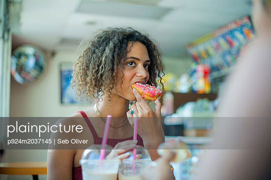 Girlfriends having doughnuts in cafe - p924m2037145 by Seb Oliver
