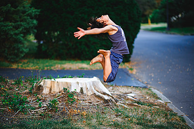 a graceful, athletic, barefoot boy leaps high in to the air in summer - p1166m2236109 by Cavan Images