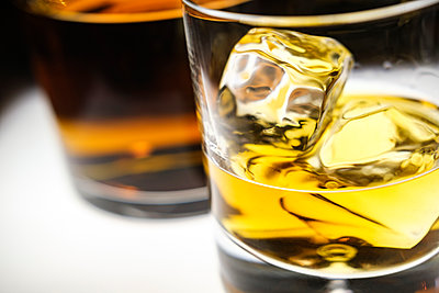 Glass of whiskey with ice cubes by bottle - p1427m2169139 by Tetra Images