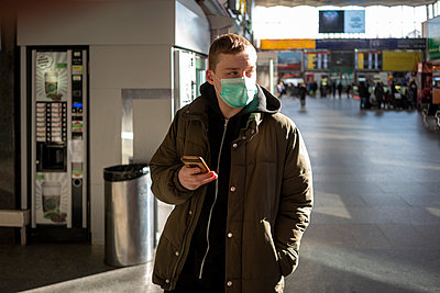 Young man with face mask at train station in the city, holding smartphone - p300m2170814 by Vasily Pindyurin