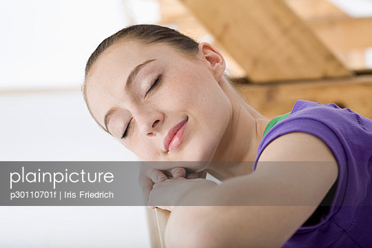 A ballet dancer resting her head on her arms at the barre in a ballet studio