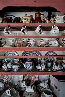 Old dresser with china teacups, saucers and plates - p1047m899854 by Sally Mundy