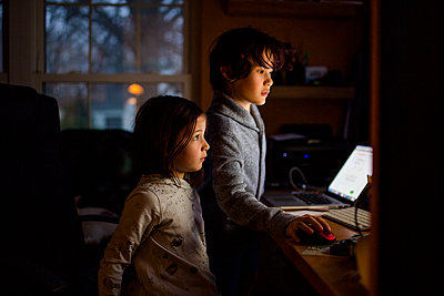 Two children stand in a dark room faces lit up by a computer screen - p1166m2190532 by Cavan Images