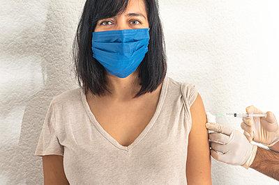 Coronavirus vaccine, woman get vaccine during coronavirus pandemic. - p1166m2236422 by Cavan Images