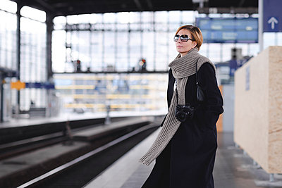 Mature woman with camera wearing black coat and large wool scarf waiting at platform - p300m2140259 by Ekaterina Yakunina