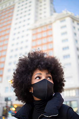 Afro young woman looking away in city during pandemic - p300m2242632 by Ignacio Ferrándiz Roig