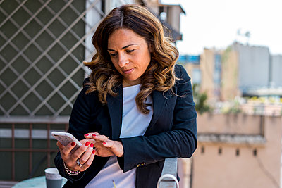 Beautiful female entrepreneur using smart phone while leaning on railing in balcony at office - p300m2264560 by VITTA GALLERY