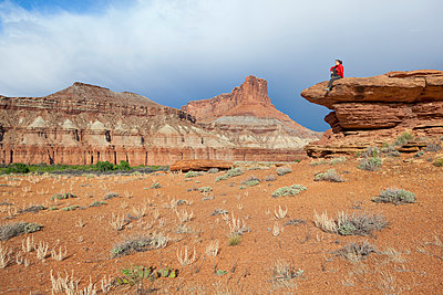 A woman sits on a terrace at Saddle Horse Bottom below tall canyon walls in Canyonlands National Park, Utah. - p343m1443463 by Ethan Welty