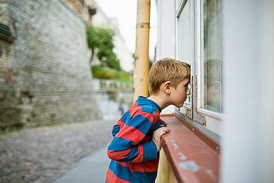 Estonia, Tallinn, Boy (6-7) looking into house through window - p352m1100888f by Jan Strandström